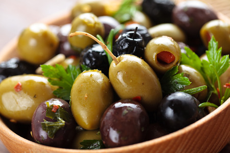 Close-up shot of marinated olives with herbs and spices in wooden plate.