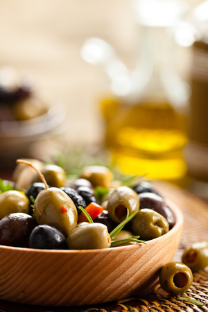 Marinated olives in wooden plate. photo