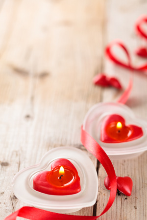 Candles, hearts and ribbon on wooden table.