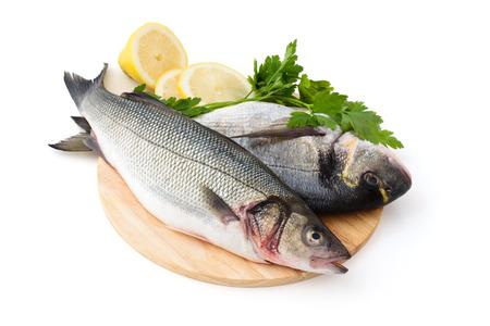 Fresh fish with lemon and parsley. Isolated on white background. photo