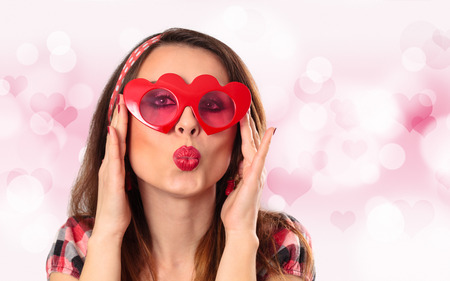 shaped: Young woman wearing heart shaped glasses against pink background. Stock Photo