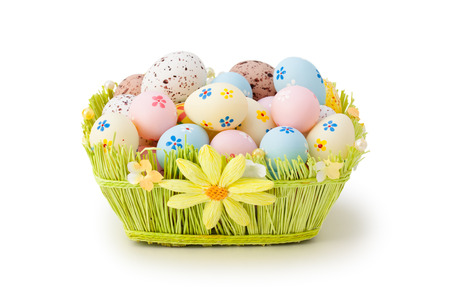 easter flowers: Colorful Easter eggs in basket. Isolated on white background. Stock Photo