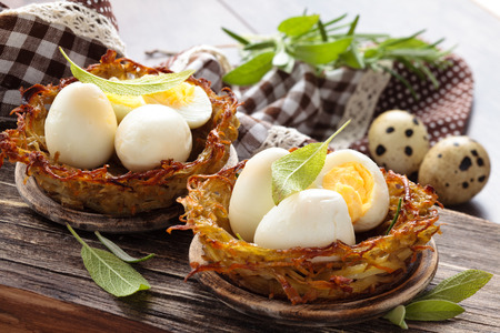 Boiled quail eggs in baked nests of potatoes. With sage and rosemary. On wooden table.