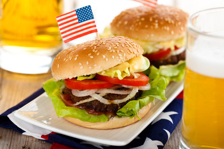 american cuisine: Beer and two tasty hamburgers with little American flags on top.
