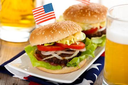 Cerveza y dos hamburguesas sabrosas con banderitas norteamericanas en la parte superior.