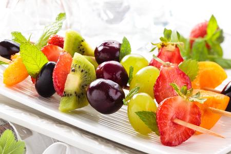 Frutas frescas de verano en los palillos. Con hojas de menta.