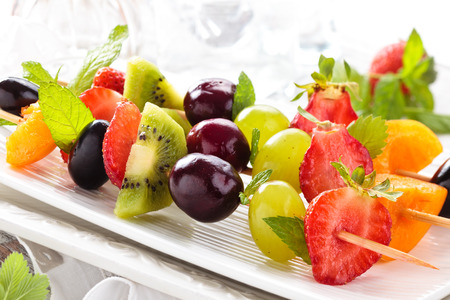 Fresh summer fruits on sticks. With mint leaves.