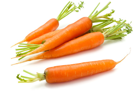 Heap of  ripe carrots with leaves. Isolated on white background.