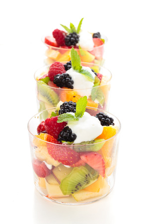 bath supplement: Fruit salad with cream and mint. In glasses. Isolated on white. Focus on raspberry and mint in the first glass.