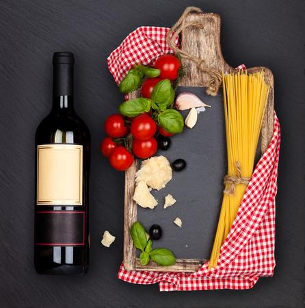 pastas: Comida italiana. Ingredientes de la pasta italiana y botella de vino a bordo de pizarra negro. Foto de archivo