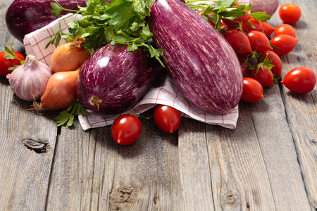 red onion: Eggplants, tomatoes, garlic and onion on rustic wooden table.