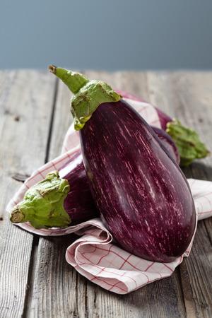 rustic food: Food ingredients. Eggplants on old rustic table.