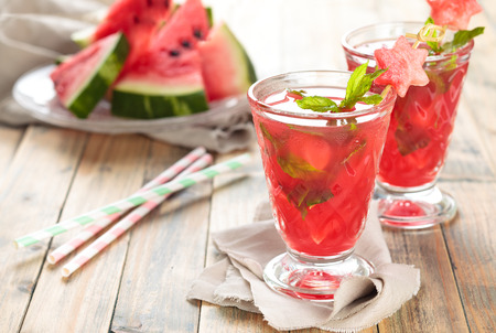 melons: Watermelon juice with mint and ice on wooden rustic  table. Stock Photo