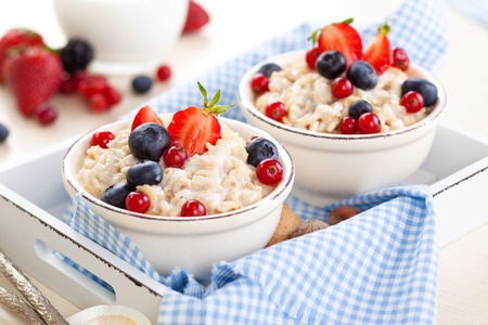 'no people': Oatmeal with fresh fruits and honey in small bowls on tray. Stock Photo