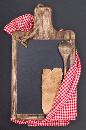 まな板、テーブル クロス、木のスプーン、作品は、古いレシピの紙します。ダーク スレート ボード。 写真素材