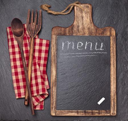 まな板、テーブル クロス、木製のスプーンやチョーク。ダーク スレート ボード。