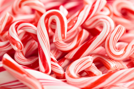 Festive red and white peppermint candycanes  background. Shallow dof.