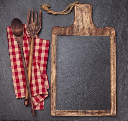 Schneidebrett, Tischdecke, Holzlöffel und Stück Kreide. Über dunklem Schieferbrett.