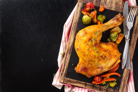 Closeup shot of baked chicken leg with thyme and vegetables on slate. Stock Photo
