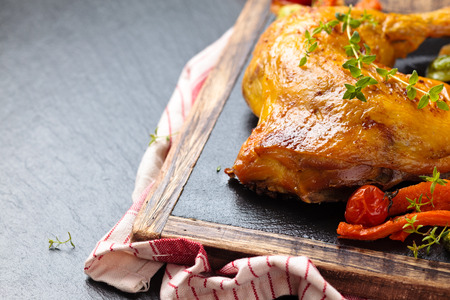 dinner menu: Closeup shot of baked chicken leg with thyme and vegetables on slate. Stock Photo