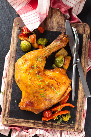 roasted chicken: Closeup shot of baked chicken leg with thyme and vegetables on slate. Stock Photo