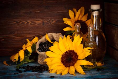 Zonnebloemen, zonnebloem olie en zonnebloempitten in rustieke achtergrond.