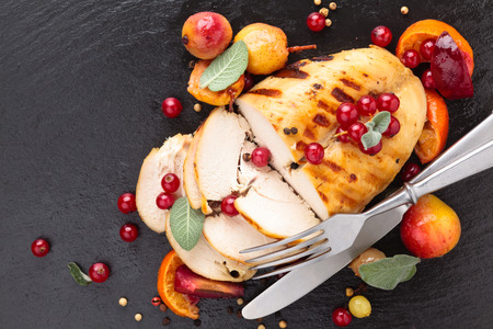 chicken breast: Closeup shot of baked chicken breast with sage and baked fruits on slate. Stock Photo