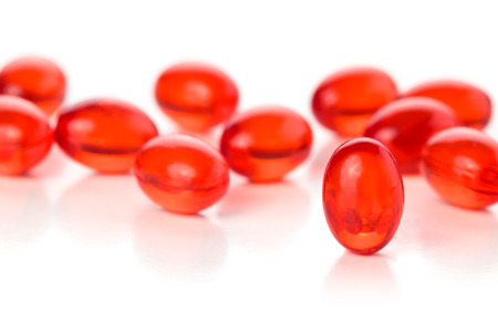 lipoprotein: Close up shot of red capsules. Isolated on white background. Stock Photo