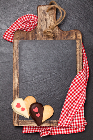 Cutting board, tablecloth, and heart-shaped cookies. Over dark slate board.