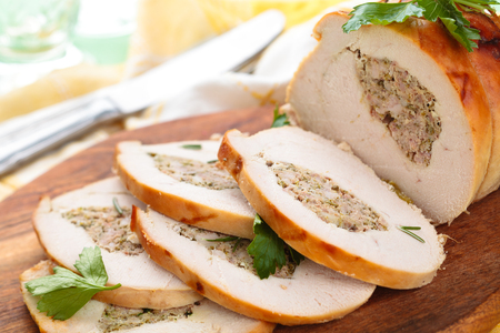 Stuffed turkey breast with parsley and rosemary on cutting board.