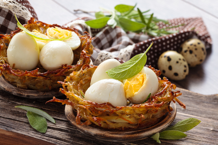 Boiled quail eggs in baked nests of potatoes. With sage and rosemary. Stock Photo