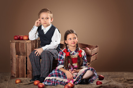 cute girl: Girl and boy with apples and boxes. Stock Photo