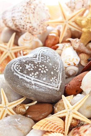 Heart shaped pebble against seashells background .