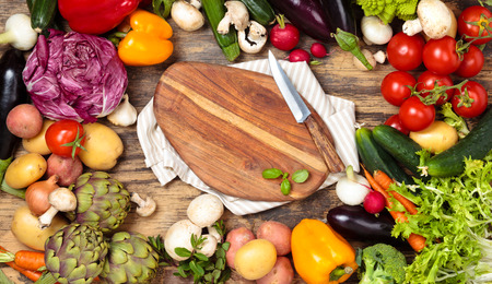 Collection of mixed organic vegetables and herbs on old wooden background.