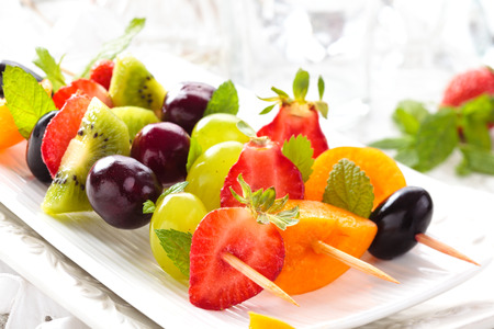 summer fruits: Fresh summer fruits on sticks. With mint leaves.