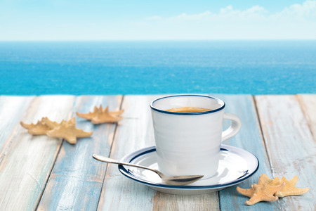 vacance: Cup of coffee on wooden table with blue sea  in background. Stock Photo