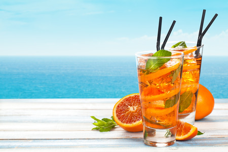 liquid summer: Refreshing lemonade with oranges and mint on wooden table. Stock Photo