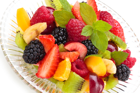 meant: Fruit salad with meant leaves in a bowl. Isolated on white background. Stock Photo