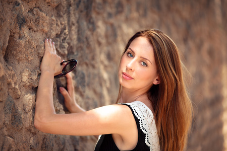 Portrait of beautiful woman standing  next to old wall.
