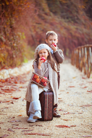 Girl and boy with an old suitcase and apples on the road.