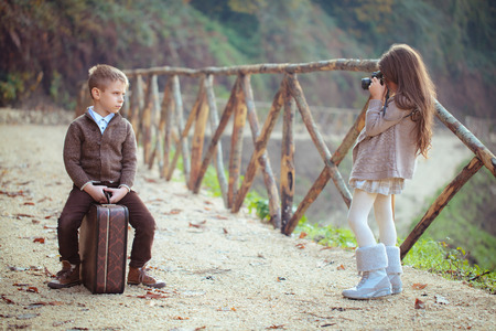 play the old park: Girl and boy with an old suitcase playing in park. Stock Photo