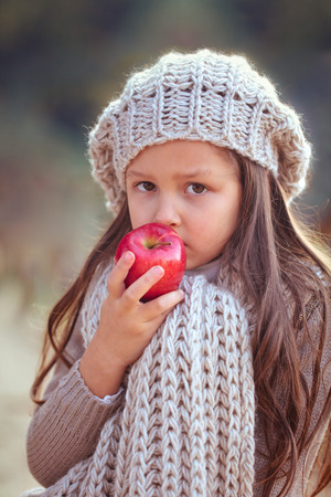 eating fruits: Beautiful girl in autumn clothes eating red apple .