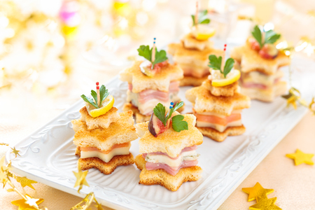 Star shaped toasts with smoked salmon,procsiutto and cheese. Stock Photo