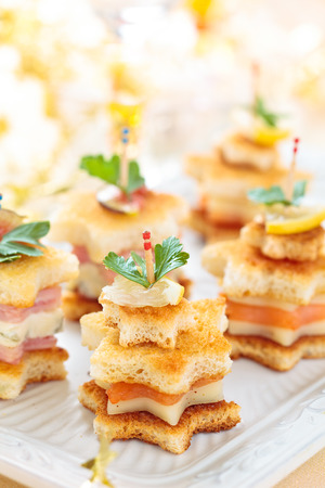 Star shaped toasts with smoked salmon,procsiutto and cheese. Banque d'images