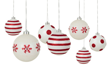 White Christmas balls with painted red patterns hanging in a row. Isolated on white background. Stock Photo
