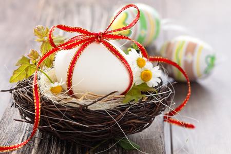 White egg in nest on wooden background.