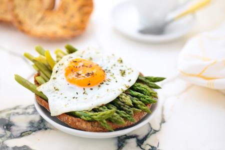 Italian food: friselli with asparagus and fried eggs. 免版税图像