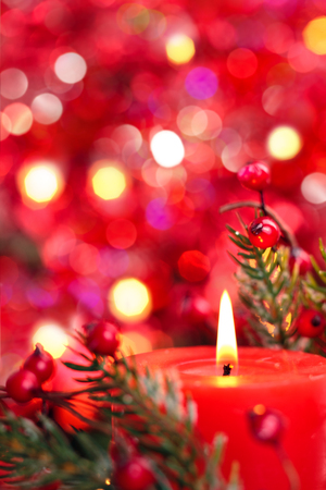 Christmas decoration with candle against red holiday lights.