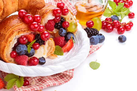 Fresh croissants with fruits. Isolated on white background