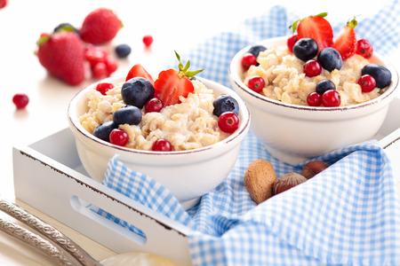 processed grains: Oatmeal with fresh fruits and honey in small bowls on tray. Stock Photo